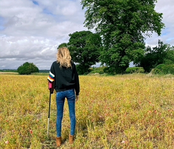 Back of woman with walking stick facing a yellow field