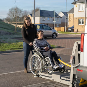 Wheelchair user pushed onto vehicle lift