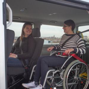 Wheelchair user in wheelchair inside vehicle alongside passenger on seat